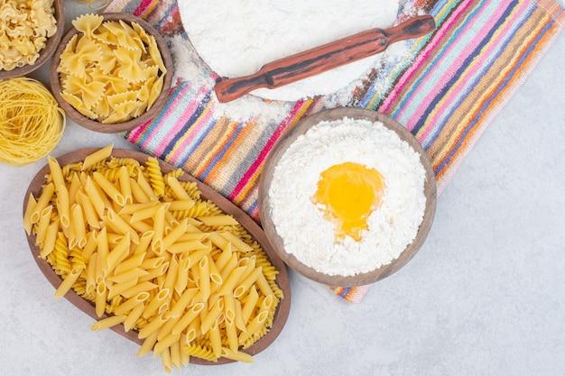 Ungekochte verschiedene nudelsorten mit mehl und rohem ei auf einer tischdecke.