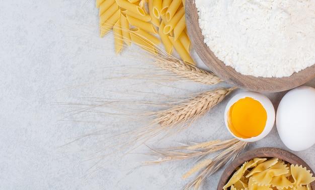 Ungekochte verschiedene nudelsorten mit mehl und rohem ei auf marmoroberfläche.