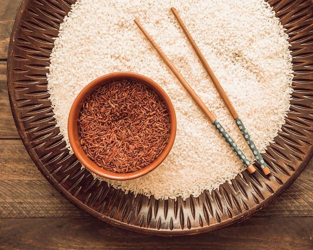 Ungekochte weiße und rote jasminreiskörner mit essstäbchen auf hölzernem behälter