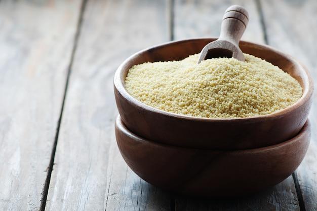 Ungekochter couscous auf dem holztisch