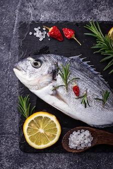 Ungekochter doradofisch mit rosmarin und gemüse. draufsicht