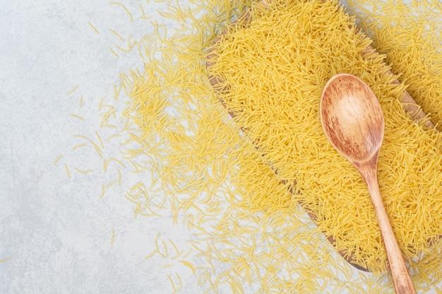 Ungekochter frischer makkaroni-löffel auf weißem raum