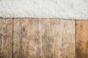 Ungekochter Reis und hölzerner Beschaffenheitshintergrund