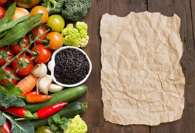 Ungekochter schwarzer reis mit gemüse und papier auf holz