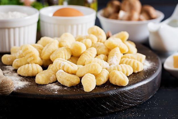 Ungekochter selbst gemachter gnocchi mit einer champignoncremesoße und einer petersilie in der schüssel