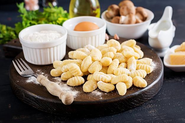 Ungekochter selbst gemachter gnocchi mit einer champignoncremesoße und -petersilie in der schüssel auf einem dunklen hintergrund.