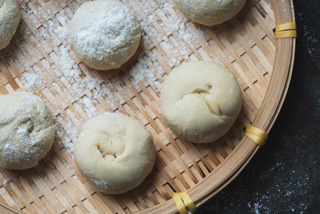 Ungekochter teig für die herstellung asiatischer brötchen auf einem traditionellen bambus-tablett. hausgemachter kochprozess. draufsicht. flache lage