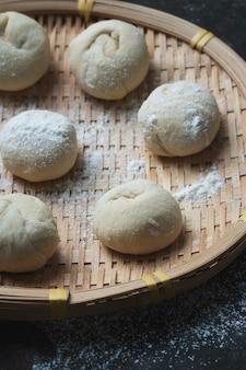 Ungekochter teig für die herstellung asiatischer brötchen auf einem traditionellen bambus-tablett. hausgemachter kochprozess. nahansicht.