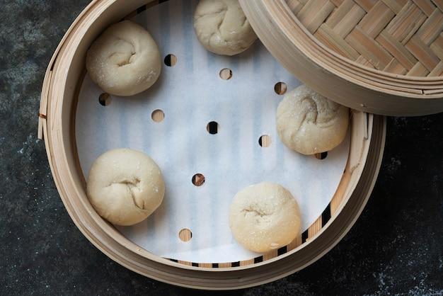 Ungekochter teig für die herstellung asiatischer brötchen im bambusdampfer. hausgemachter kochprozess. draufsicht. flache lage