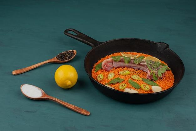 Ungekochtes fleisch mit roten linsen, pfefferscheiben, knoblauch und spinat in einer schwarzen pfanne mit zitrone und gewürzen.
