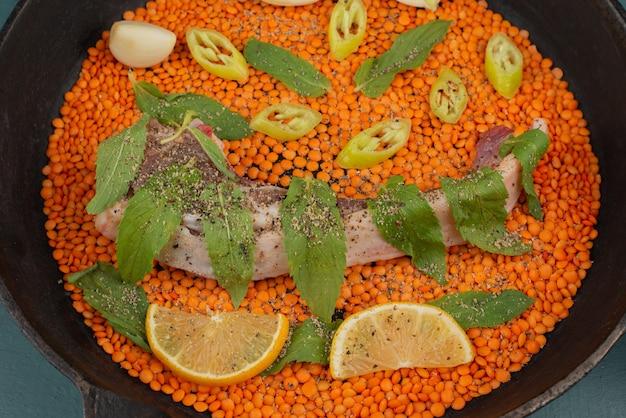 Ungekochtes fleisch mit roter linse, pfefferscheiben, knoblauch und spinat in einer schwarzen pfanne.