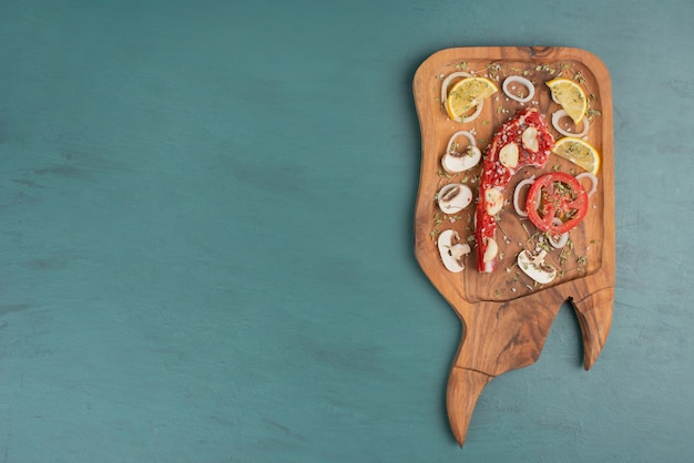 Ungekochtes fleischstück mit gemüse auf blauem tisch.