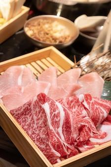 Ungekochtes, frisch geschnittenes schweinefleisch und rindfleisch in einer quadratischen holzkiste, die sich auf shabu vorbereitet