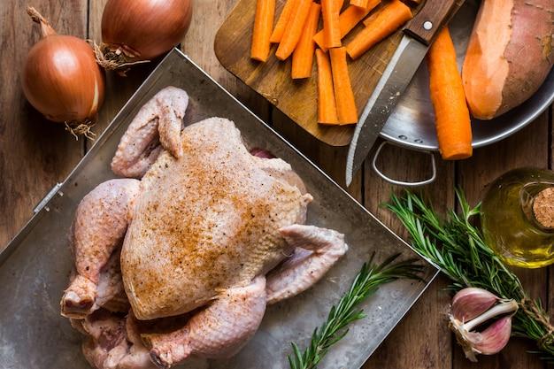 Ungekochtes hähnchen, gewürzt mit rosmarin, gehacktem gemüse, karotten, kartoffeln, zwiebeln, knoblauch