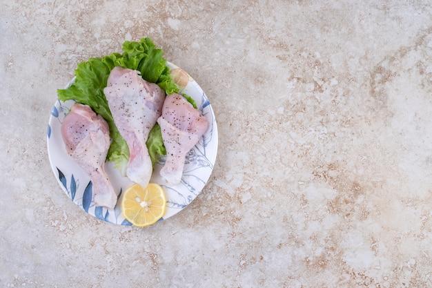 Ungekochtes hähnchenschenkelfleisch mit salat und zitrone