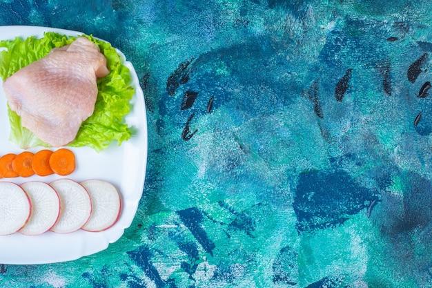 Ungekochtes hühnerfleisch neben tomaten, rettich und karotten auf einem teller