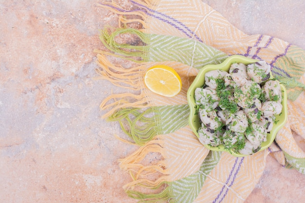 Ungekochtes kaukasisches khinkali mit gehackten kräutern in einer schüssel.