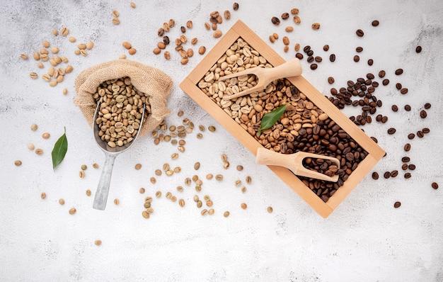 Ungeröstete und dunkel geröstete kaffeebohnen aus grünem und braunem decaf in holzkiste mit schaufeln auf weißem beton.