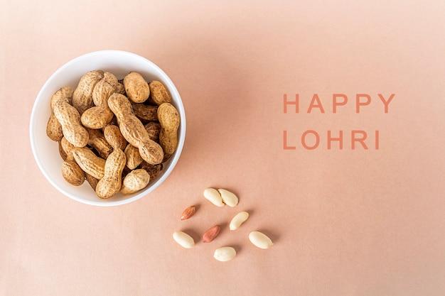 Ungeschälte erdnüsse in weißer schüssel beim entlassen. leckerbissen für das indisch-kanadische punjabi-fest von lohri