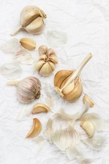 Ungeschälte knoblauchzehe, knoblauchzehen und schale. natürliches bäuerliches essen. . flach liegen