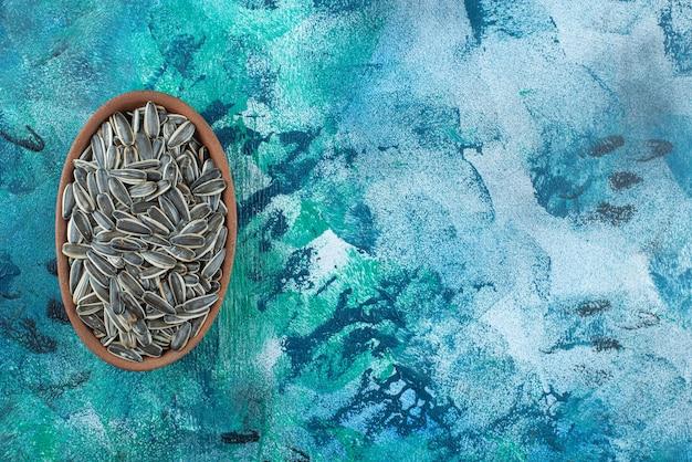 Ungeschälte sonnenblumenkerne in einer tonschale auf dem marmortisch.