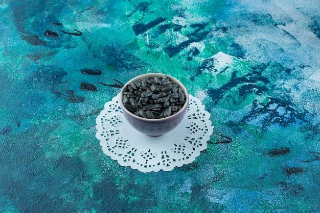 Ungeschälte sonnenblumenkerne in schalen auf untersetzer, auf dem blauen tisch.