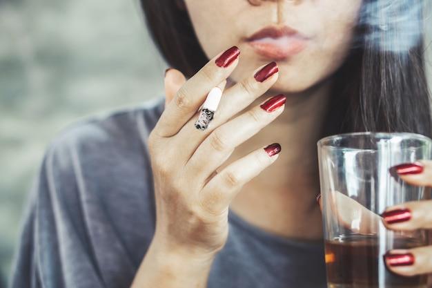Ungesunde asiatische frau, die alkohol raucht und trinkt