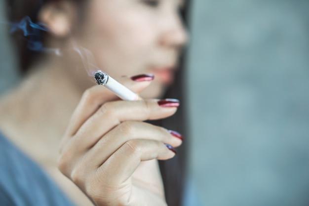 Ungesunde frau, die zigarette raucht