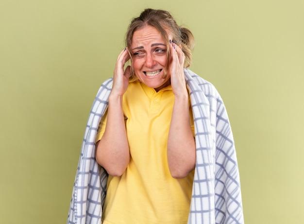 Ungesunde frau in decke gehüllt, die sich unwohl fühlt und an grippe und erkältung leidet, fieber hat und unter starken kopfschmerzen leidet