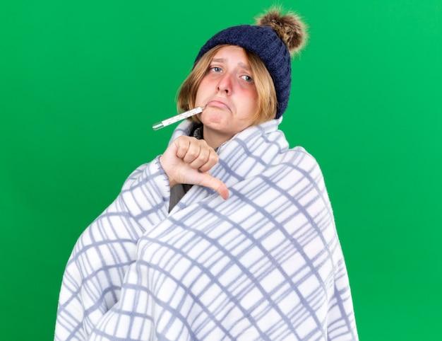 Ungesunde junge frau, die in eine decke gehüllt ist und einen hut trägt, der ihre körpertemperatur mit einem thermometer misst, das an grippe leidet und fieber hat, das die daumen nach unten zeigt, die über der grünen wand stehen?