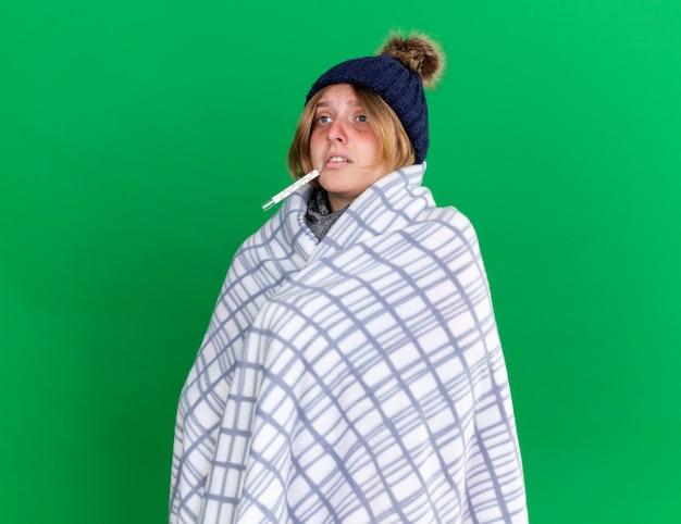 Ungesunde junge frau, die in eine decke gehüllt ist und einen hut trägt, der ihre körpertemperatur mit einem thermometer misst, das an grippe leidet und fieber hat, das über der grünen wand steht?