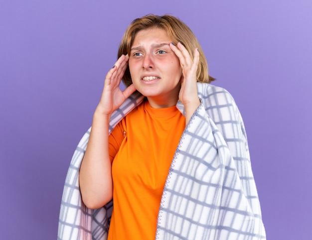 Ungesunde junge frau, die in eine warme decke gehüllt ist und an grippe und kopfschmerzen leidet und fieber hat, die ihre temperatur mit einem thermometer misst, das besorgt aussieht