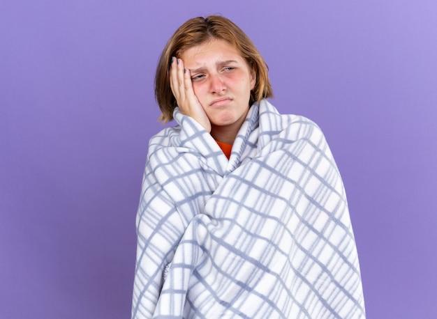 Ungesunde junge frau, eingewickelt in eine warme decke, die sich krank fühlt und an grippe leidet, fieber und starke kopfschmerzen hat, die über lila wand steht?