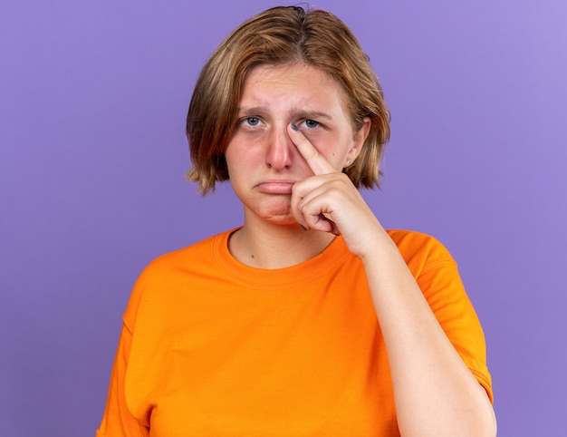 Ungesunde junge frau in orangefarbenem t-shirt, die sich schrecklich fühlt und schwer an viren leidet