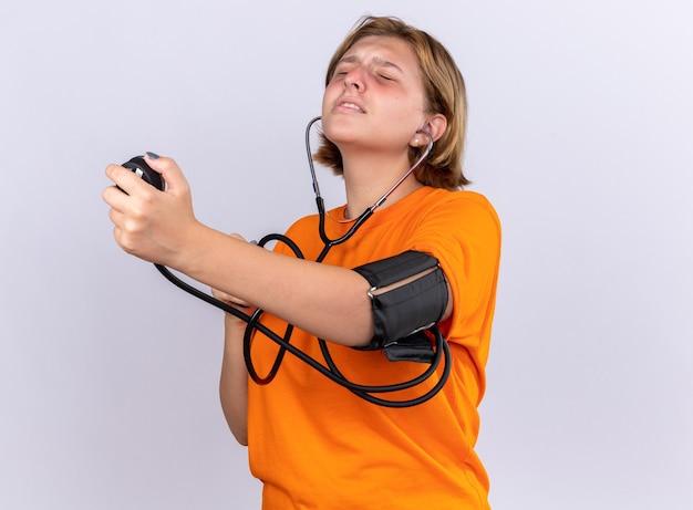 Ungesunde junge frau in orangefarbenem t-shirt, die sich unwohl fühlt, indem sie den blutdruck mit einem tonometer misst und besorgt über der weißen wand steht