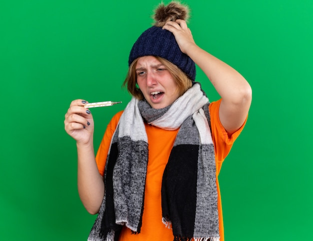 Ungesunde junge frau in orangefarbenem t-shirt mit hut und warmem schal um den hals, die sich schrecklich fühlt, wenn sie ein fieberthermometer hat, das an grippe leidet und enttäuscht aussieht looking