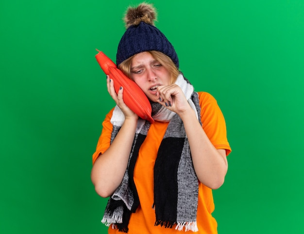 Ungesunde junge frau in orangefarbenem t-shirt mit hut und warmem schal um den hals, die sich schrecklich fühlt, wenn sie eine wärmflasche hält, die an erkältung leidet