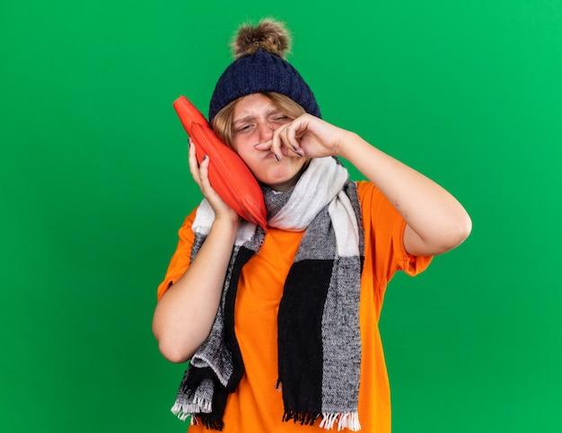 Ungesunde junge frau in orangefarbenem t-shirt mit hut und warmem schal um den hals, die sich schrecklich fühlt, wenn sie eine wärmflasche hält, die unter kalter nase wischt