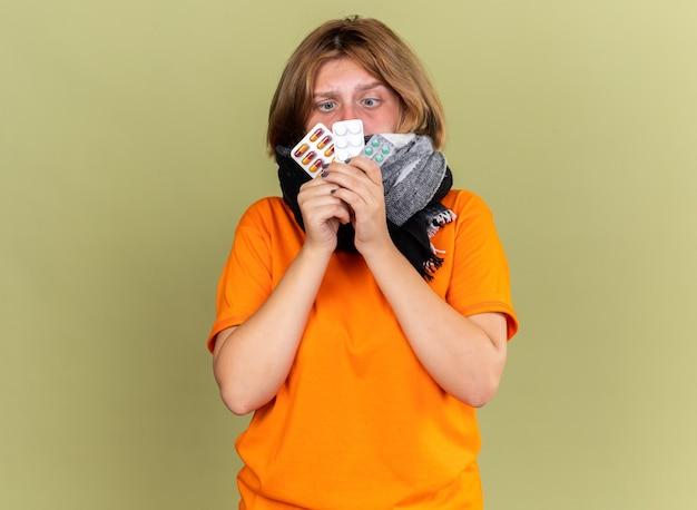 Ungesunde junge frau in orangefarbenem t-shirt mit warmem schal um den hals, die sich unwohl fühlt und an grippe leidet, die verschiedene pillen hält, die verwirrt aussehen
