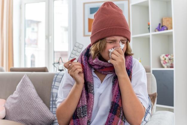 Ungesunde junge frau in warmem hut mit schal bläst nase im gewebe, die an erkältung und grippe leidet und auf dem stuhl im hellen wohnzimmer sitzt living