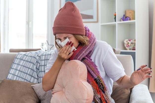 Ungesunde junge frau in warmem hut mit schal mit kissen, die nase in gewebe bläst und an erkältung und grippe leidet, sitzt auf dem stuhl im hellen wohnzimmer