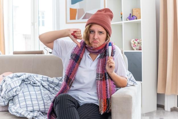 Ungesunde junge frau in warmer mütze mit schal um den hals, die thermometer hält und daumen nach unten schürzt, sitzt auf der couch im hellen wohnzimmer