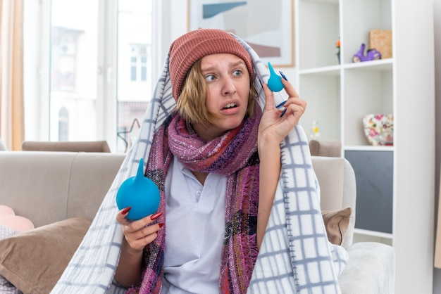 Ungesunde junge frau mit hut in decke gewickelt, die sich unwohl und krank fühlt und einläufe hält, die verwirrt aussehen und zweifel haben, die auf der couch im hellen wohnzimmer sitzen