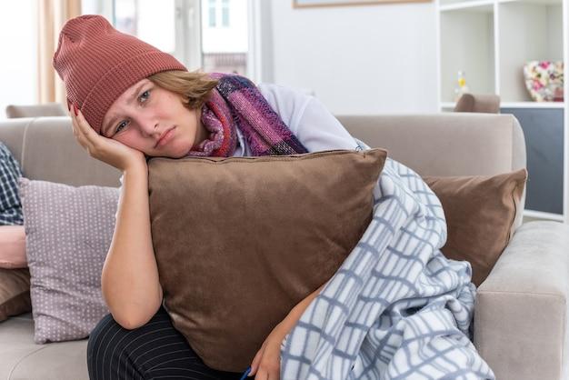 Ungesunde junge frau mit hut mit warmem schal um den hals, die sich unwohl fühlt und ein kissen hält, das an erkältung und grippe leidet, mit traurigem ausdruck auf der couch im hellen wohnzimmer sitzend