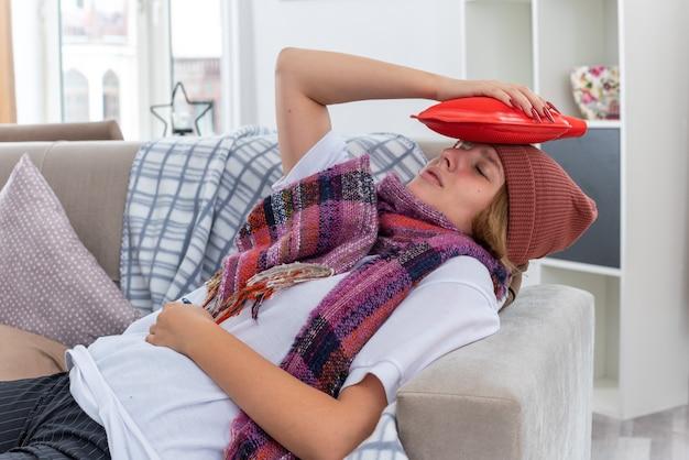 Ungesunde junge frau mit hut mit warmem schal um den hals, die sich unwohl und krank fühlt und an erkältung und grippe leidet, die eine wärmflasche auf dem kopf hält und besorgt auf der couch im hellen wohnzimmer liegt