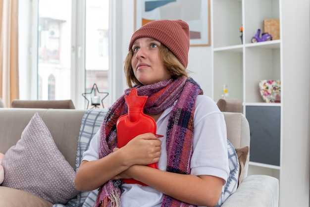 Ungesunde junge frau mit hut mit warmem schal um den hals, die sich unwohl und krank fühlt und an erkältung und grippe leidet, die eine wärmflasche hält und besorgt auf der couch im hellen wohnzimmer sitzt