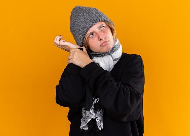 Ungesunde junge frau mit warmem hut und schal um den hals, die an erkältung und grippe leidet und ihren puls mit ernstem gesicht über der orangefarbenen wand überprüft