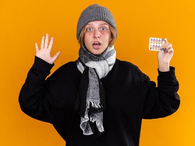 Ungesunde junge frau mit warmem hut und schal um den hals, die schrecklich an erkältung und grippe leidet und pillen hält, die besorgt über der orangefarbenen wand stehen?