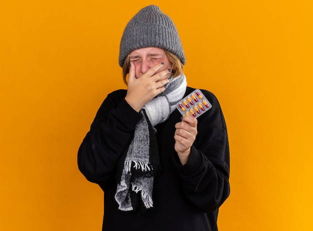 Ungesunde junge frau mit warmem hut und schal um den hals, die schrecklich an erkältung und grippe leidet und pillen hält, die den mund mit der hand über der orangefarbenen wand niesen