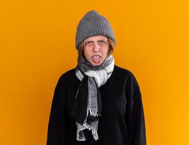 Ungesunde junge frau mit warmem hut und schal um den hals, die sich krank fühlt und an erkältung und grippe leidet, die die zunge mit angewidertem ausdruck über der orangefarbenen wand herausstreckt